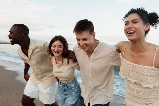 Amigos sorridentes de tiro médio na praia