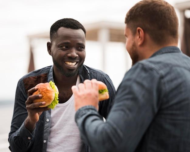 Amigos sorridentes de tiro médio segurando hambúrgueres