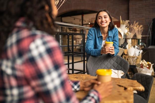Amigos sorridentes em um café aproveitando o tempo