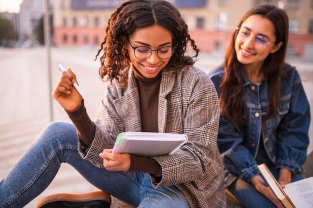 Amigos sorridentes fazendo lição de casa lá fora