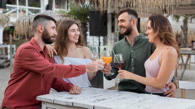 Amigos sorridentes fazendo um brinde médio