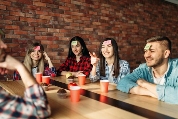 Amigos sorridentes jogando notas de adesivo para jogo de testa.