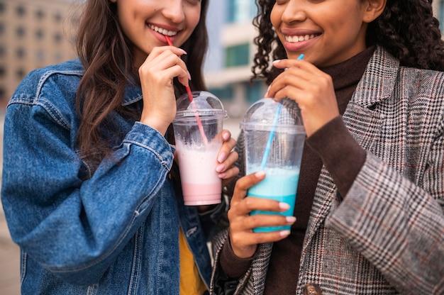 Amigos sorridentes juntos ao ar livre com milkshakes