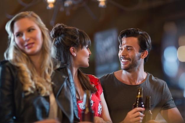 Amigos sorridentes, olhando um para o outro, segurando garrafas de cerveja.