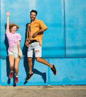 Amigos sorridentes pulando com fundo azul
