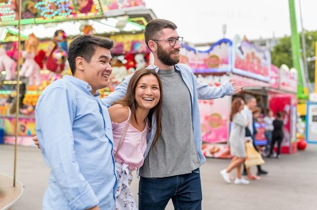 Amigos sorridentes se abraçando no parque de diversões