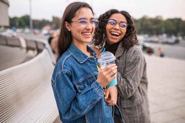 Amigos sorridentes se divertindo juntos ao ar livre com milkshakes