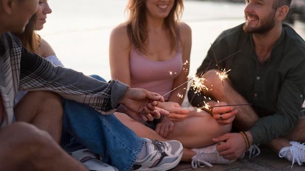 Amigos sorridentes segurando fogos de artifício em close-up