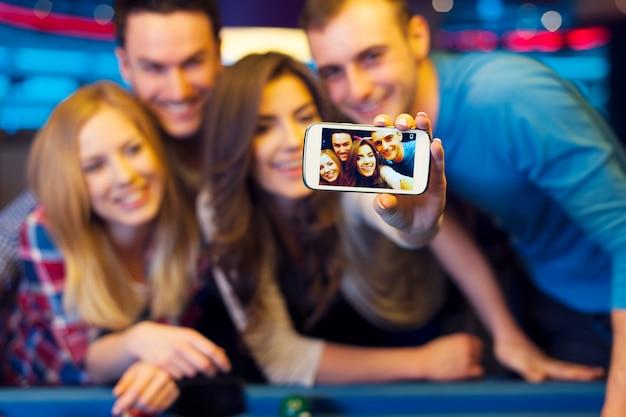 Amigos sorridentes tirando uma selfie em uma boate com bilhar
