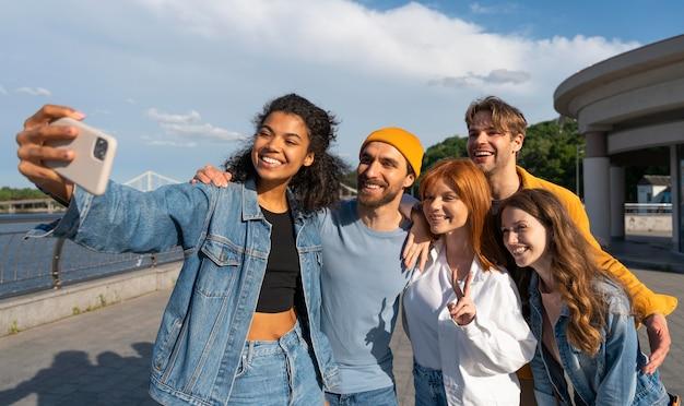 Amigos sorridentes tirando uma selfie juntos, foto média