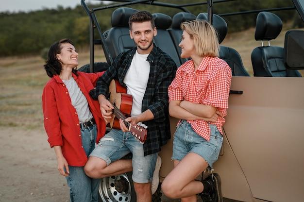 Amigos sorridentes tocando guitarra enquanto viajam de carro