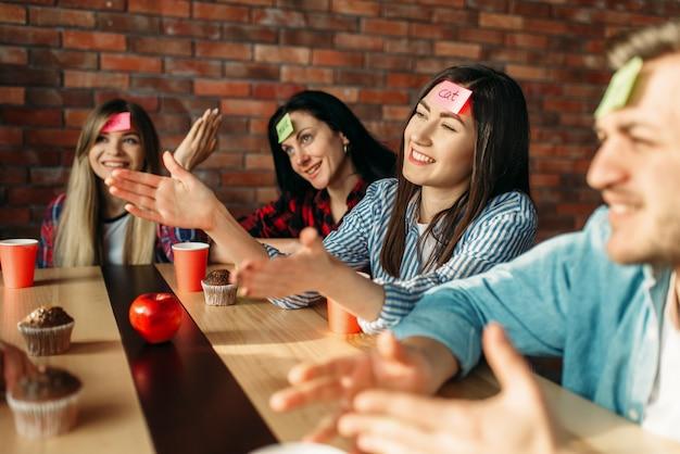 Amigos sorridentes tocando notas de adesivos na testa