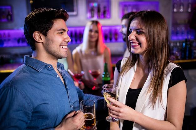 Amigos sorridentes tomando copo de cerveja e vinho no balcão de bar