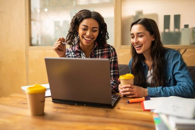 Amigos sorridentes usando laptop para fazer o dever de casa enquanto tomam café