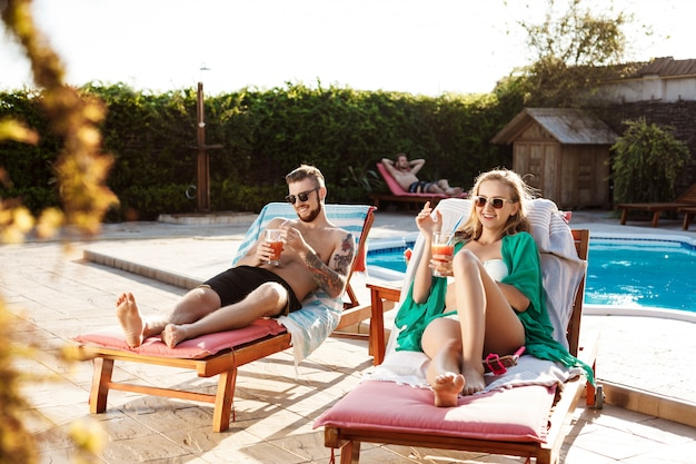 Amigos, sorrindo, bebendo cocktails, deitado nas espreguiçadeiras perto da piscina