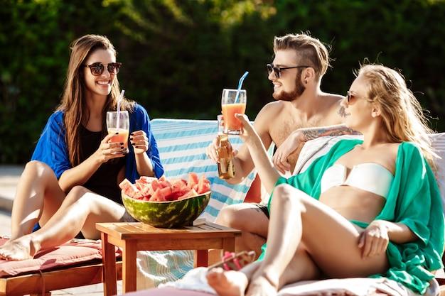Amigos sorrindo, comendo melancia, bebendo cocktails, relaxando perto da piscina