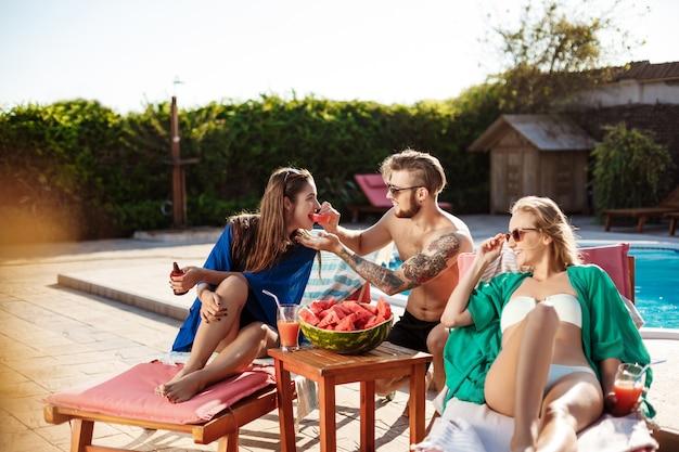 Amigos sorrindo, comendo melancia, relaxando, deitado perto da piscina