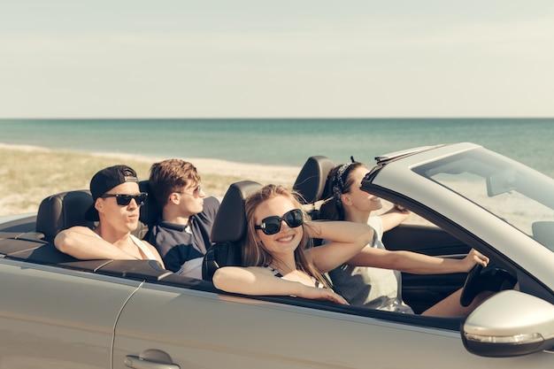 Amigos sorrindo, dirigindo o carro perto do mar e se divertindo