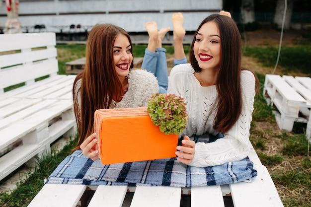 Amigos, sorrindo e segurando um presente