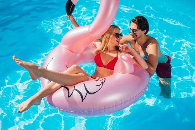 Amigos, sorrindo, em, um ao outro, em, piscina