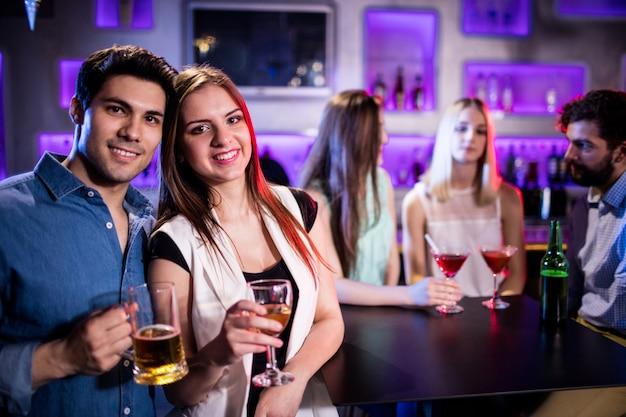 Amigos sorrindo, tomando uma taça de vinho e cerveja no bar