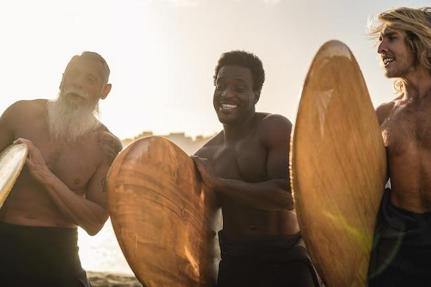 Amigos surfistas multirraciais se divertindo na praia após a sessão de surf - foco suave na mão do homem africano