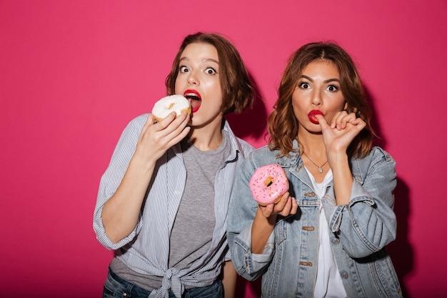 Amigos surpreendentes de duas mulheres comendo rosquinhas