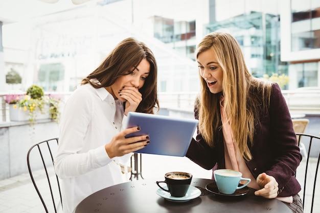 Amigos surpresos, olhando para tablet no café