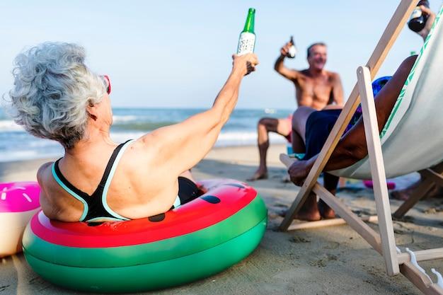 Amigos, tendo uma bebida, praia