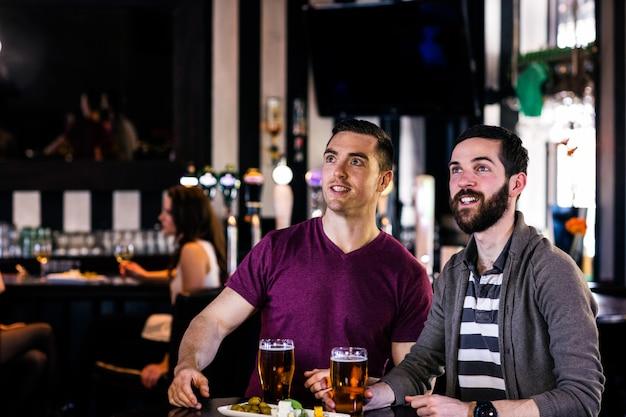 Amigos, tendo uma cerveja e assistindo tv em um bar
