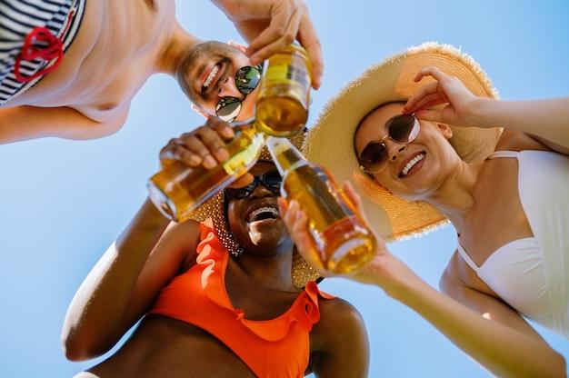 Amigos tilintam garrafas com cerveja, vista de baixo