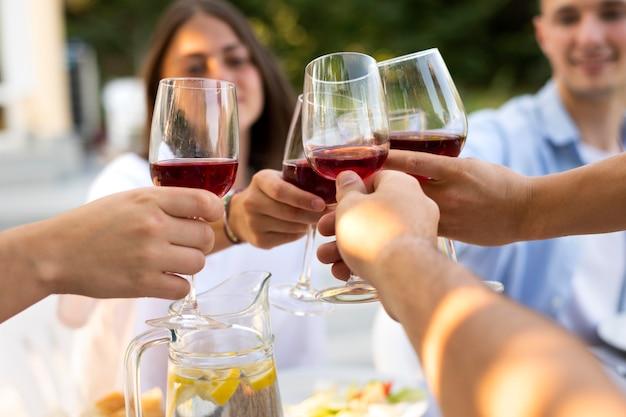Amigos tilintando taças de vinho de perto