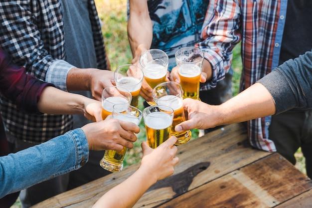 Amigos tilintando uma garrafa de cerveja durante o acampamento ao ar livre