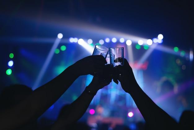 Amigos tilintar de copos de bebida em um bar moderno