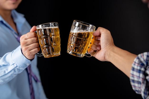 Amigos tinindo canecas de cerveja