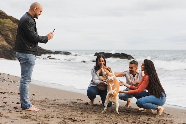 Amigos tirando foto com cachorro