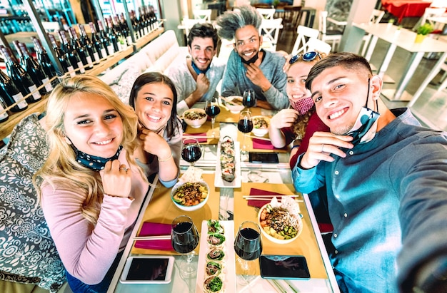 Amigos tirando selfie com máscaras faciais em restaurante sushi bar