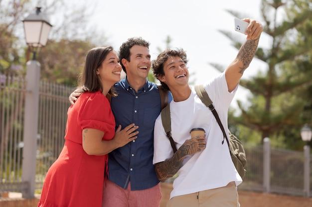 Amigos tirando selfie com telefone médio tiro