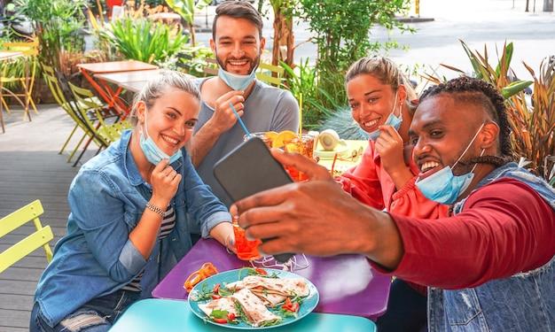 Amigos tirando selfie em um bar restaurante com máscara facial na hora do coronavírus - jovens se divertindo com bebidas e lanches ao ar livre com novas regras após a quebra do vírus