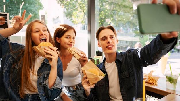 Amigos tirando selfie enquanto comem fast food