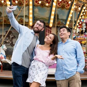 Amigos tirando selfie no parque de diversões