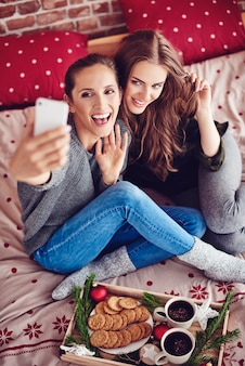 Amigos tirando uma selfie no quarto