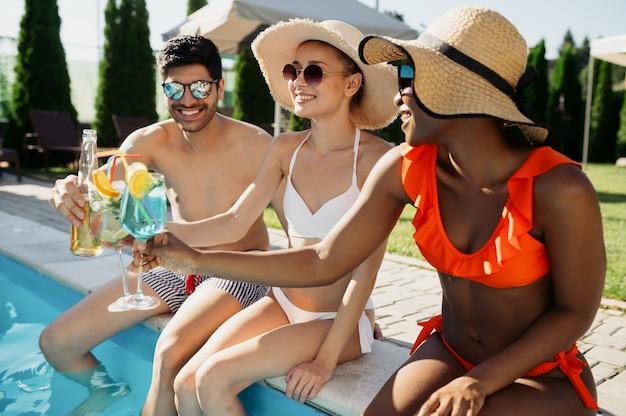 Amigos tomam bebidas na beira da piscina