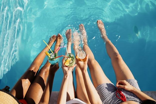 Amigos tomam bebidas na piscina, vista de cima