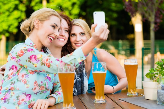 Amigos tomando selfie com smartphone no jardim da cerveja