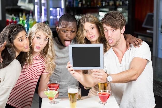 Amigos tomando selfie com um tablet