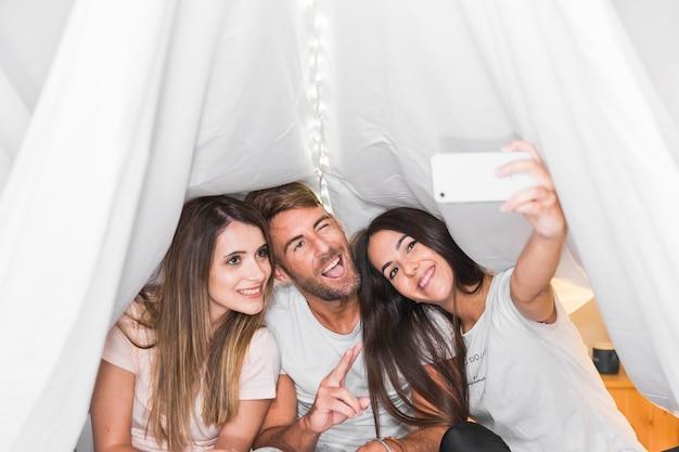 Amigos tomando selfie no celular sentado sob a cortina
