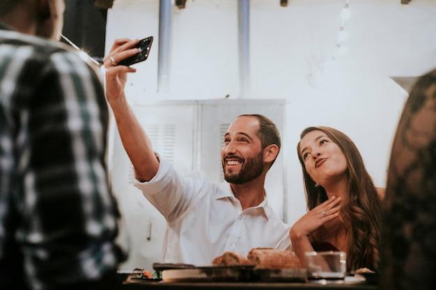 Amigos tomando uma selfie em um jantar