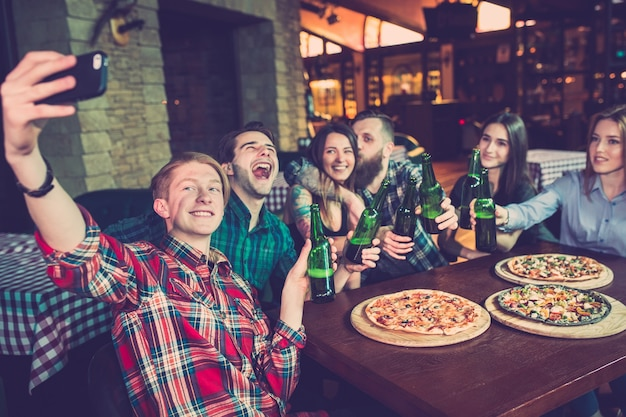 Amigos, tomar uma bebida em um bar e comer pizzas