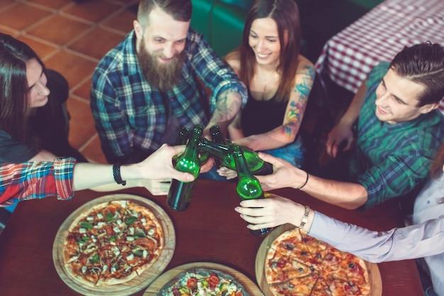 Amigos, tomar uma bebida em um bar, eles estão sentados em uma mesa de madeira com cervejas e pizza.